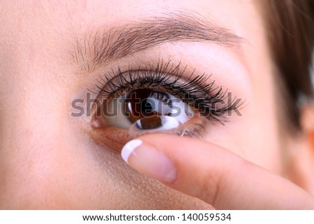 Young woman putting contact lens in her eye close up - stock photo