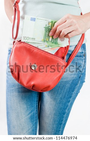 Young woman putting Euro banknotes in a handbag - stock photo
