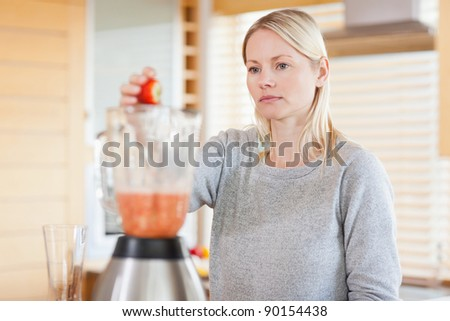 Young woman putting fruits into the blender - stock photo