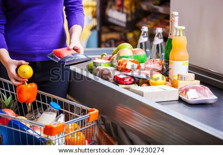 Young woman putting goods on counter in supermarket - stock photo