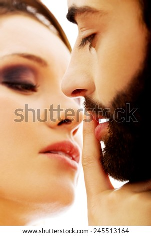 Young woman putting her finger on man's lips. - stock photo