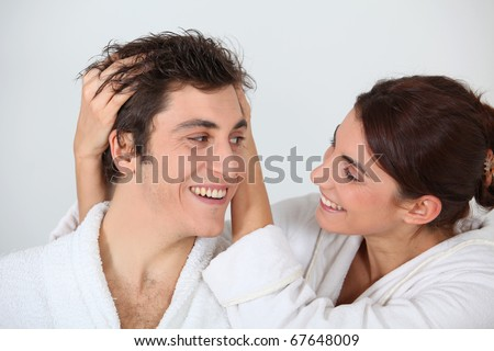 Young woman putting her hands in her boyfriend's hair - stock photo