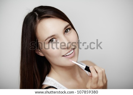 young woman putting lip gloss on with a big smile on her face - stock photo