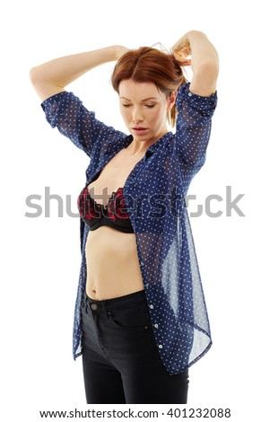 Young woman putting on her shirt, wearing black and red bra, shoot over white background, isolated - stock photo