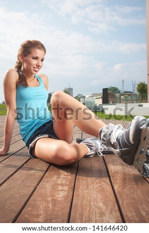 Young woman putting on skates going rollerblading in urban city park. - stock photo