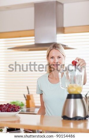 Young woman putting strawberry into the blender