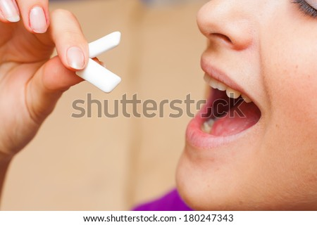 Young woman putting two chewing gum pellets in her mouth.