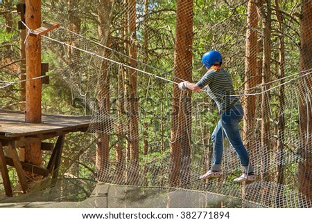 Young woman puzzled in adventure rope park - stock photo