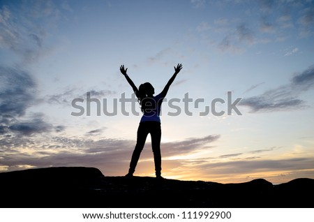 Young woman raising her hands while standing on stone of coastline in the sunrise. - stock photo