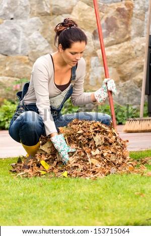 Young woman raking dry leaves pile backyard housework fall - stock photo