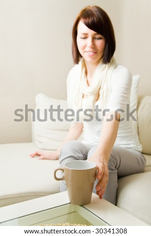 Young woman reaching for a coffee mug