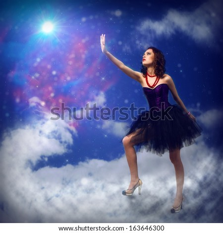 Young woman reaching for a glowing star, around abstract background
