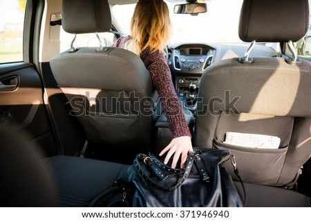 Young woman reaching purse from back seat - rear view - stock photo