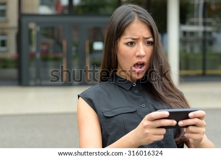 Young woman reacting in horror to an sms, text message or email on her mobile phone as she stands outdoors in a quiet urban street, close up head and shoulders - stock photo