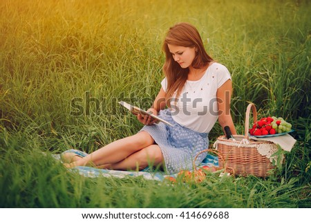 Young woman read a book outdoors. Basket with berries behind - stock photo