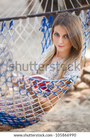 Young woman read the book in the hammock - stock photo