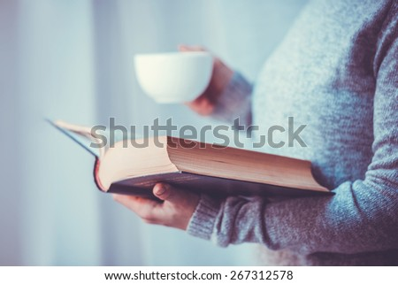 Young woman reading a book and holding cup of tea or coffee. Toned image - stock photo