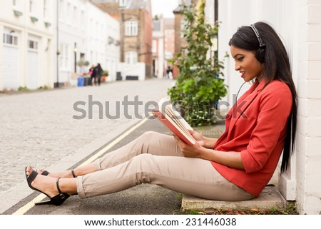 young woman reading a book and listening to music. - stock photo