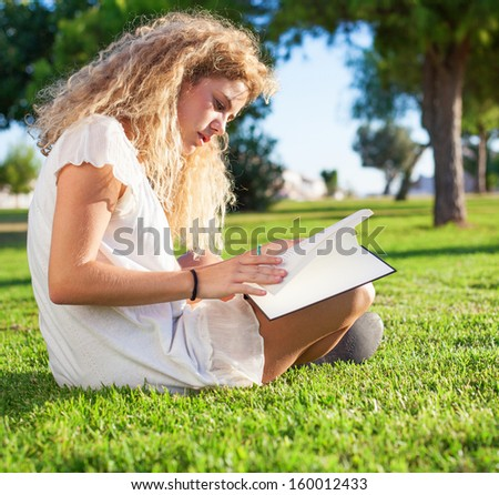 young woman reading a book at park on sunny day