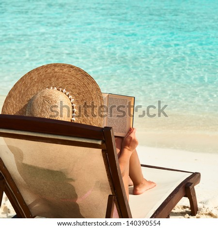 Young woman reading a book at the beach - stock photo