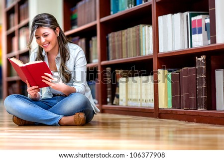 Young woman reading a book at the library - stock photo