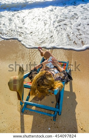Young woman reading a book at the tropical  beach - stock photo
