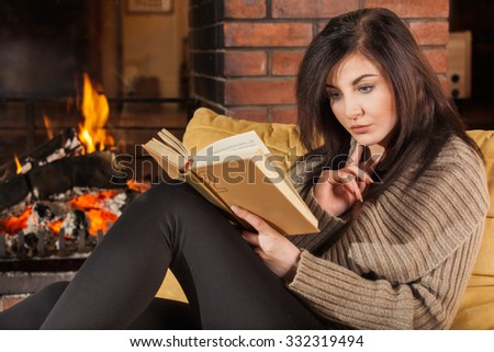 Young woman reading a book by fireplace - stock photo