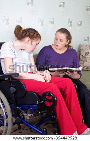 Young woman reading a book girl in a wheelchair.
