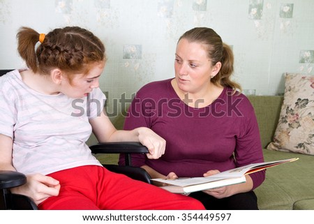 Young woman reading a book girl in a wheelchair