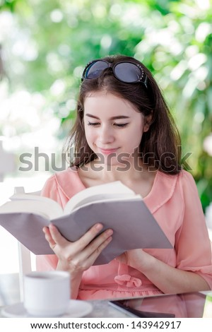 young woman reading a book in outdoor coffee shop