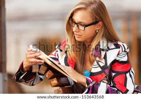 Young woman reading a book in park - stock photo