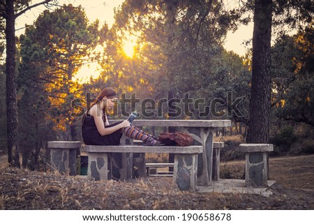 Young woman reading a book in the forest - stock photo