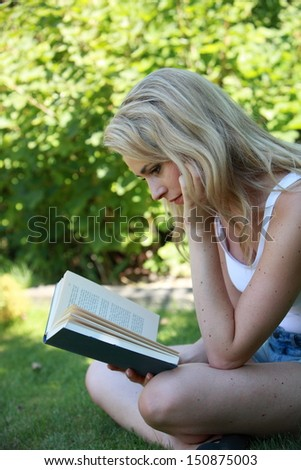 Young woman reading a book in the garden sitting sideways cross legged on the grass concentrating on the story