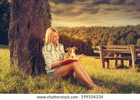 Young woman reading a book in the nature with her dog - stock photo