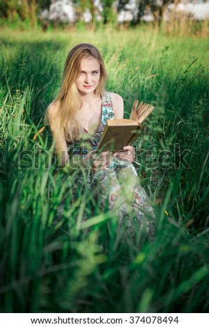 Young woman reading a book in the shade of a tree in the midst of green meadows. - stock photo