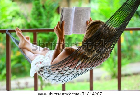 Young woman reading a book lying in a hammock - stock photo