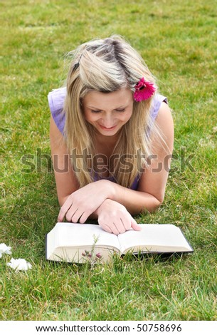 Young woman reading a book lying on the grass in a park