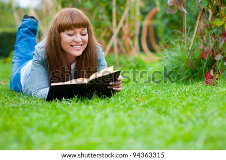 Young woman reading a book lying on the grass in the park