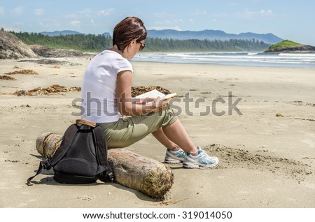 Young Woman Reading a Book on a Deserted Beach in Tofino, BC, Canada