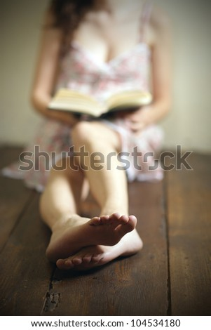 young woman reading a book on the old wooden floor