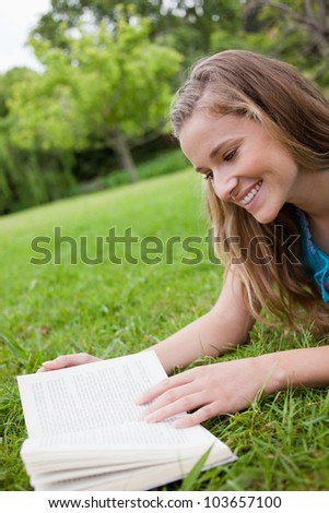 Young woman reading a book while lying on the grass in a parkland and smiling - stock photo