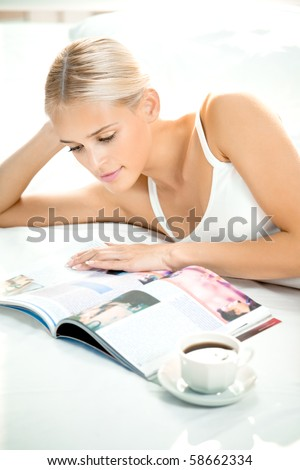 Young woman reading a magazine at bedroom - stock photo