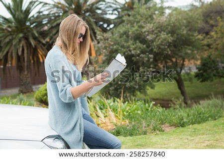 Young woman reading a map beside her car - stock photo