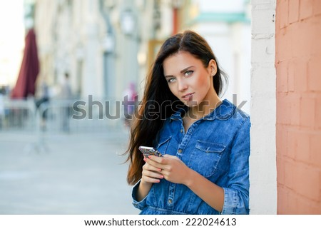 Young woman reading a message on the phone in a summer street