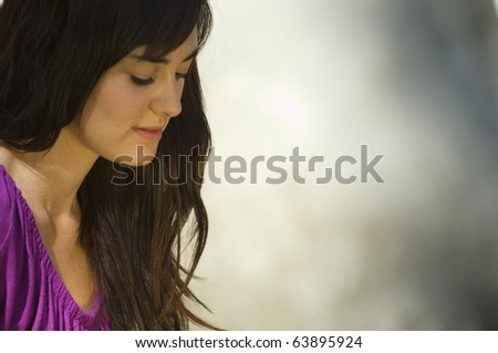 Young woman reading bible by river in summer - stock photo