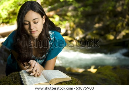 Young woman reading bible by stream in summer - stock photo