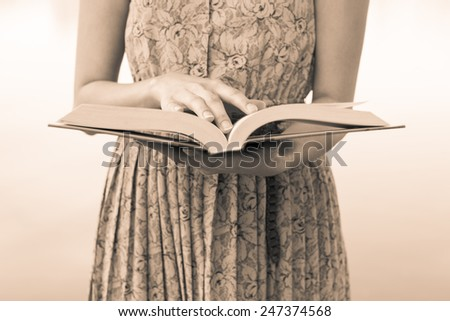 Young woman reading bible in natural park - stock photo