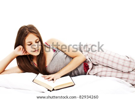 Young woman reading book in bed. Isolated on white background.