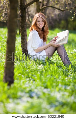 Young woman reading book in summer park. - stock photo