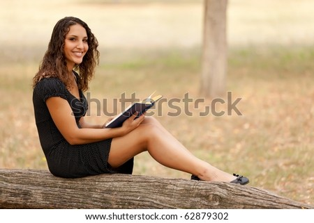 young woman reading book sitting on trunk tree